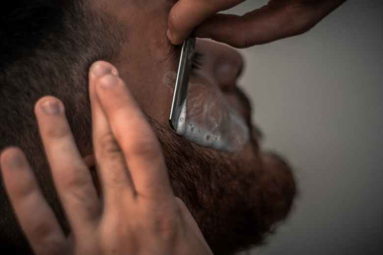 person holding gray straight razor